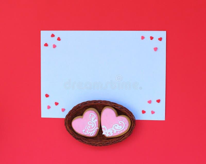 Presentes modernos da composição em um envelope branco com dois corações cor-de-rosa na cesta no fundo vermelho imagem de stock