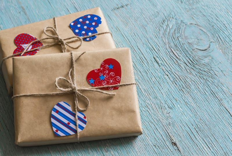 Presentes no papel de embalagem, corações de papel do dia de Valentim na superfície de madeira azul imagens de stock