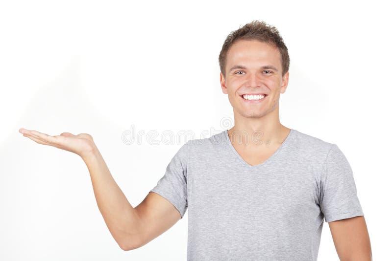 Presentes sonrientes del hombre con una palma abierta foto de archivo libre de regalías