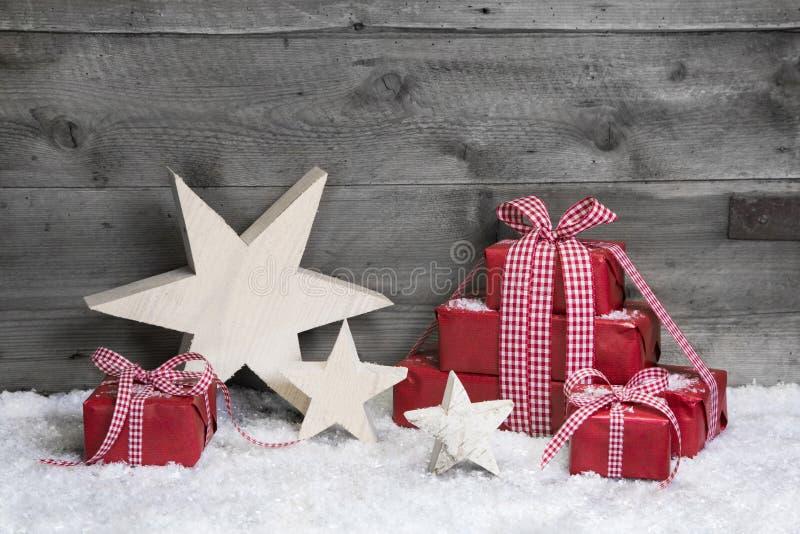 Presentes vermelhos do Natal com começos de madeira no fundo de madeira cinzento imagem de stock