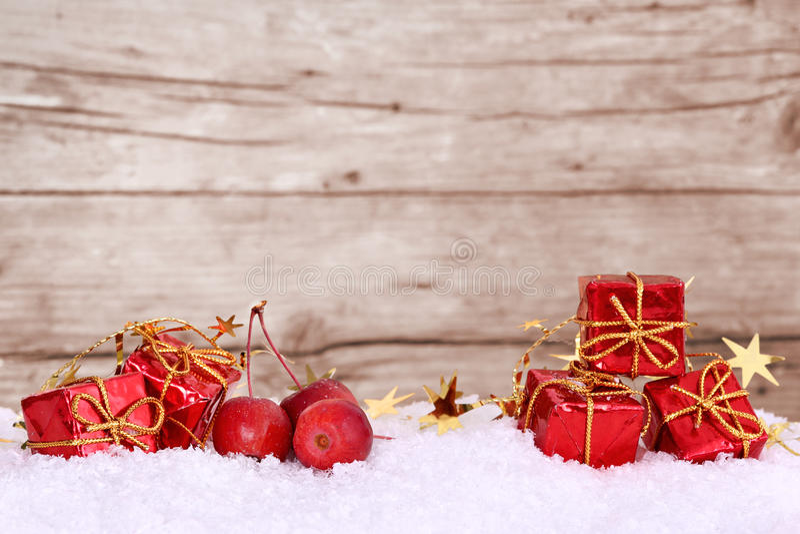Presentes y manzanas en la nieve, espacio para el texto imagenes de archivo