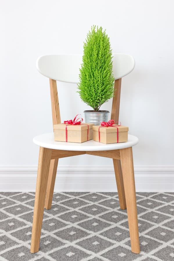 Presentes y poco árbol verde en una silla blanca fotografía de archivo