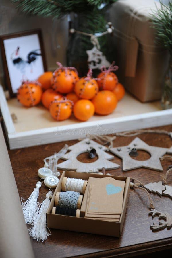 Presenti con la decorazione di Natale Ramo dell'albero di Natale in un vetro Spostamento di regalo con la carta kraft Mandarini c fotografia stock