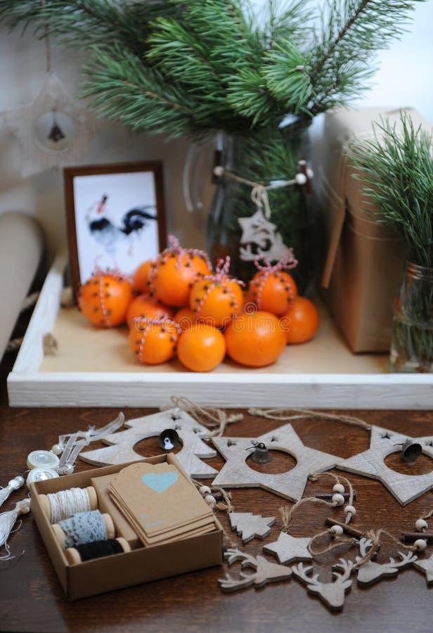 Presenti con la decorazione di Natale Ramo dell'albero di Natale in un vetro Spostamento di regalo con la carta kraft Mandarini c fotografie stock