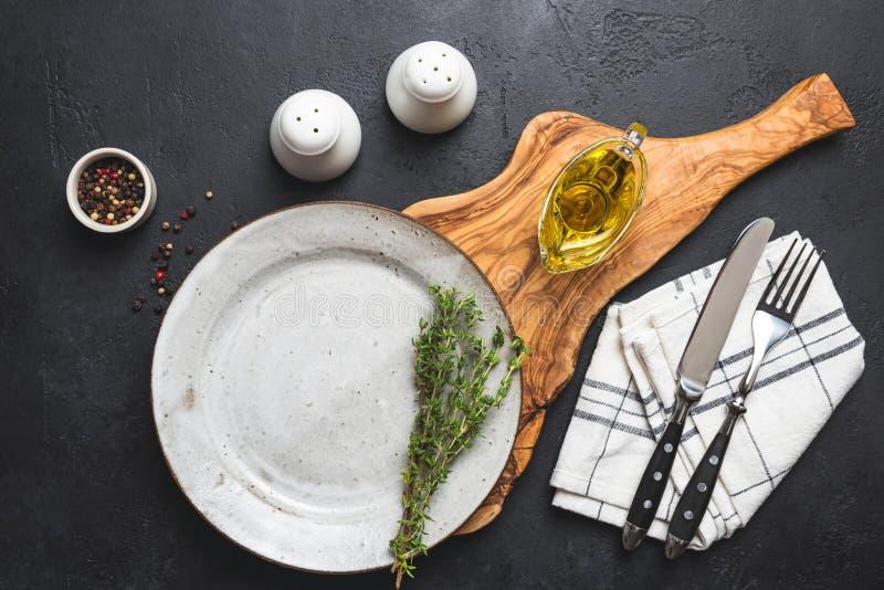 Presenti la regolazione con il piatto, la coltelleria, il tessuto e le spezie vuoti fotografie stock