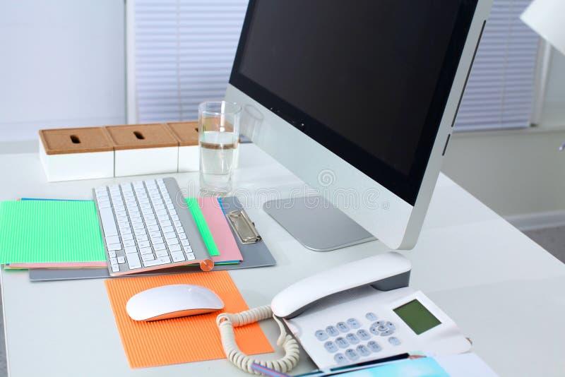 Presenti lo spazio di funzionamento del progettista con un computer e un lavoro di ufficio fotografie stock