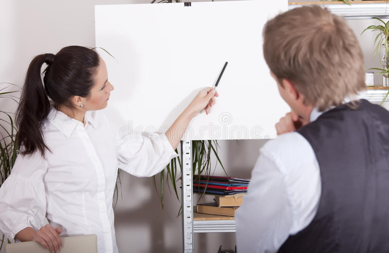 Presenting on billboard. Woman pointing with a pen on white billboard in office stock images