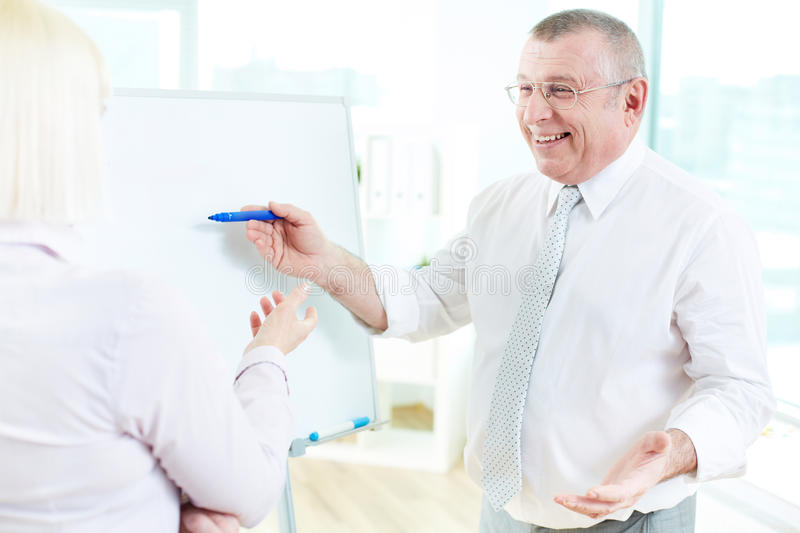 Presenting ideas. Happy mature businessman teaching his partner on whiteboard at meeting royalty free stock images