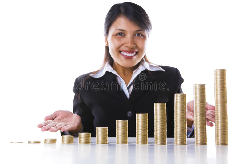 Presenting investment profit growth. Young businesswoman in background presenting a bar graph of investment profit growth in twelve months made from stacks of royalty free stock images