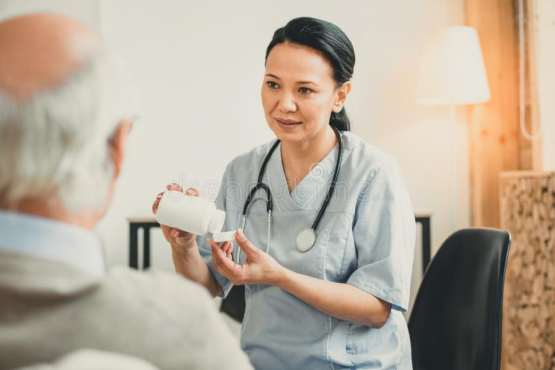 Pretty woman with brown eyes carrying bottle of pills. Presenting new medicines. Pretty women with brown eyes carrying bottle of pills sitting with her old ward royalty free stock image