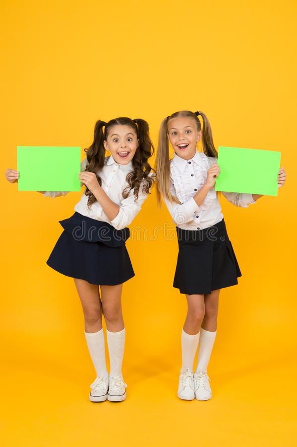 Presenting product. Happy little girls holding blank green papers for product advertising on yellow background. Back to. School product. More information about stock photography