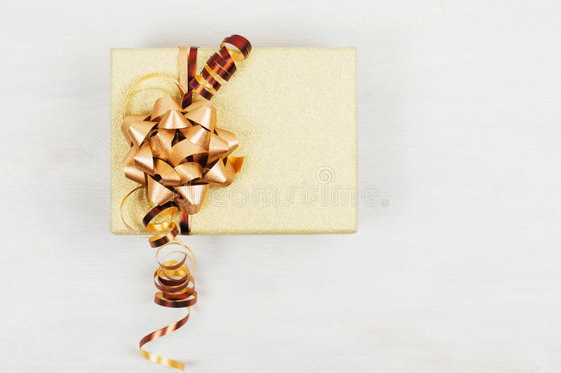 Presents box with golden ribbon. On white wooden background. Flat lay, rustic style royalty free stock photos