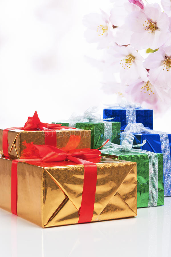Presents and Celebration Concepts. Many Colorful Wrapped Up Gift Boxes. Standing In Line Together. Against Flowery Abstract Background. Vertical Image stock photography