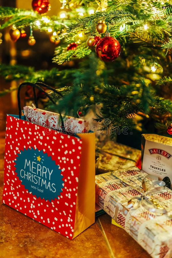 Presents And Chocolate Candies Waiting To Be Opened Under Christmas Tree royalty free stock image