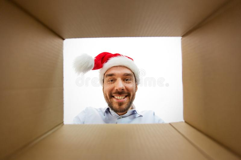 Happy man opening parcel box or christmas gift. Presents, delivery and holidays concept - happy man in santa helper hat looking into open parcel box or christmas royalty free stock photo