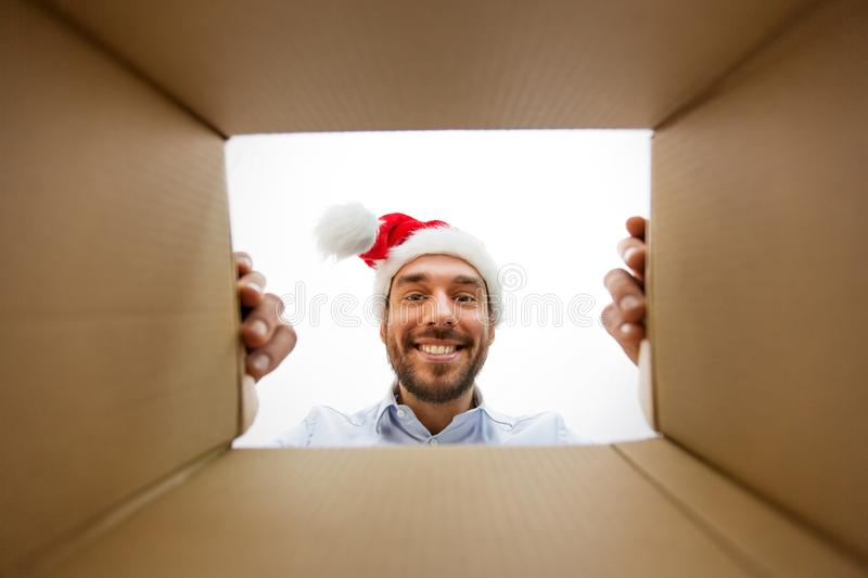 Happy man opening parcel box or christmas gift. Presents, delivery and holidays concept - happy man in santa helper hat looking into open parcel box or christmas stock photo
