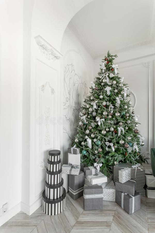 Presents and Gift boxes under Christmas Tree. Boxes with ribbon bow. New year decorated house interior. Winter Holiday royalty free stock photos