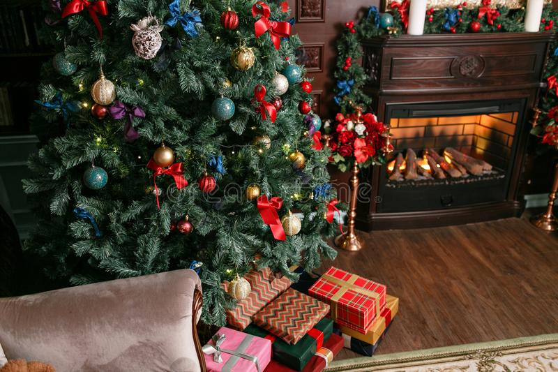 Presents and Gift boxes under Christmas Tree. Colorful boxes with ribbon bow. New year decorated house interior. Winter stock images