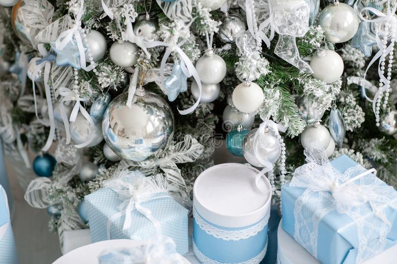Presents and Gifts under decorated Christmas Tree. Happy new year. Christmas morning in bright living room royalty free stock photo
