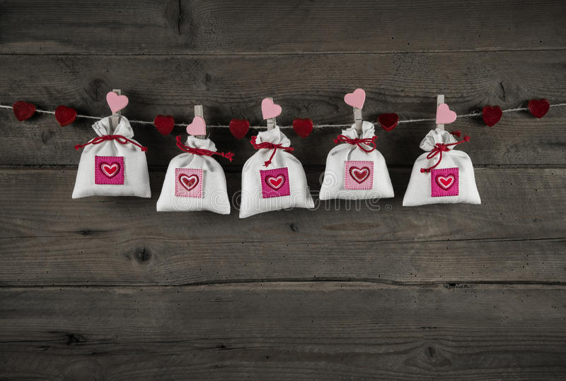 Presents with hearts hanging on wooden background for celebrations. stock photo