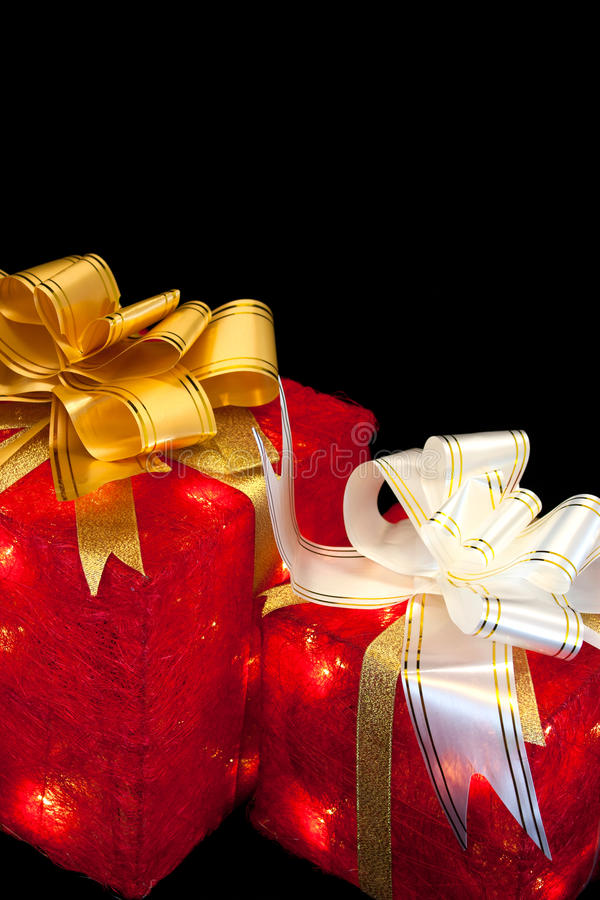 Presents with lights. Two red presents with yellow and white ribbons, with glowing lights stock photo