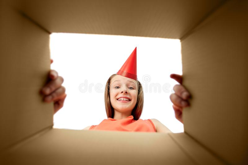Happy birthday girl in party hat opening gift box. Presents and surprise concept - happy surprised birthday girl in party hat opening gift box royalty free stock images