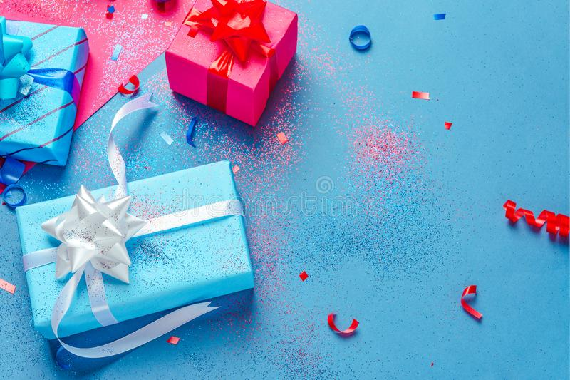 Presents wrapped in brightly colored blue pink and red paper with glitter  ribbons and other decorations royalty free stock image