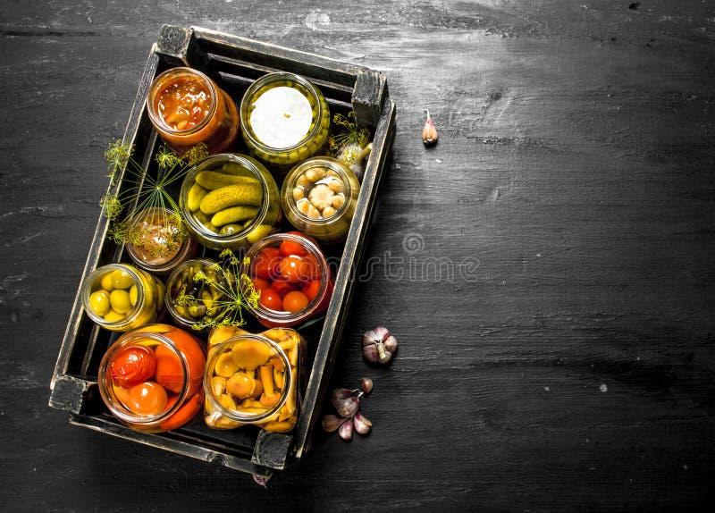 Preserva vegetais nos frascos de vidro em uma caixa velha imagens de stock