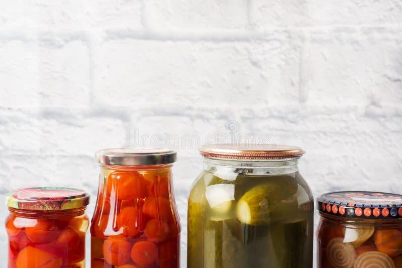 Preservación de verduras en los bancos Productos de la fermentaci?n Cosecha de los pepinos y de los tomates para el invierno Copi imagen de archivo