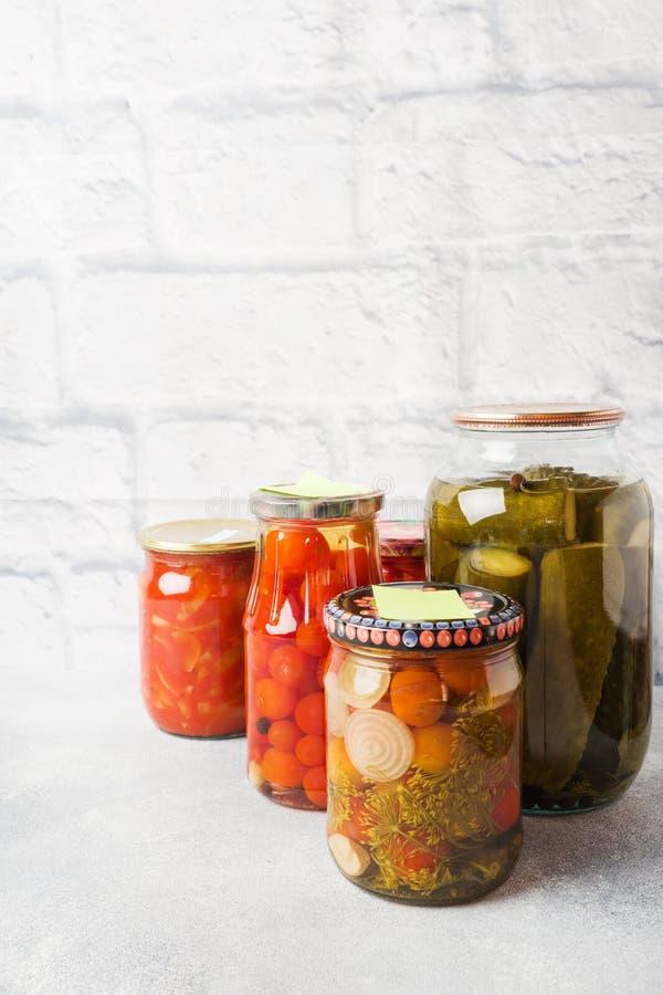 Preservación de verduras en los bancos Productos de la fermentaci?n Cosecha de los pepinos y de los tomates para el invierno Copi fotos de archivo