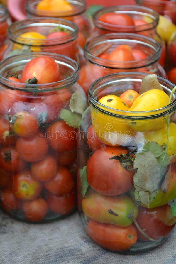 Preservation. Blanks for the winter. Marinated tomatoes. Red and yellow tomatoes in jars. Pepper. Vertical photo stock image