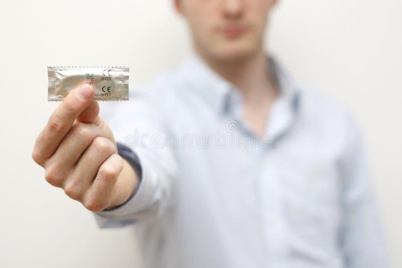 Preservativo della holding dell'uomo fotografia stock
