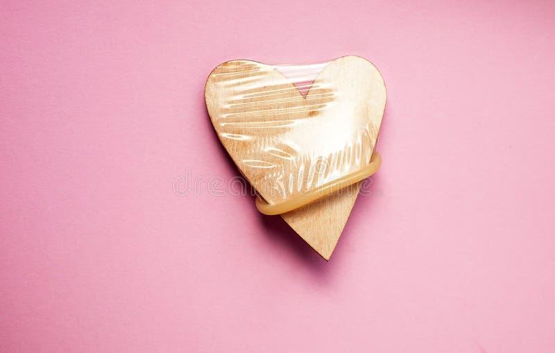 Preservativo indossato sul cuore di legno Concetto del sesso sicuro fotografia stock