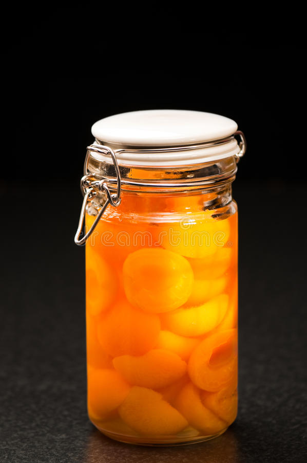 Preserved Apricots. In kilner jar on kitchen worktop, light from window on side of jar stock photography