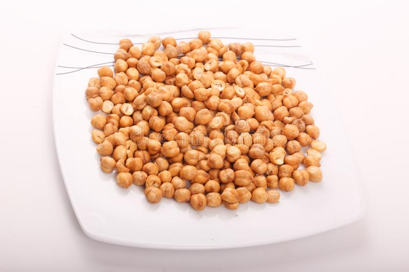 Chickpeas on white dish. Preserved chickpeas on white modern dish, top view stock image