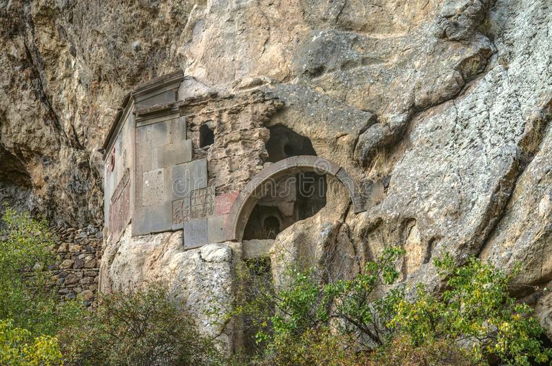 Preserved corner and arched entrance to the cave church in the rock near the territory of Geghard monastery of Armenia royalty free stock images