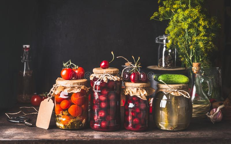 Preserved and fermented  food in glass jars - pickles, jam, compote with tomatoes, cucumber and cherries on dark rustic background. Fermented food. Autumn stock image