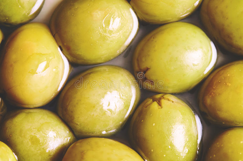 Preserved pickled green olives. Closeup of pickled green olives background. Top view stock photo