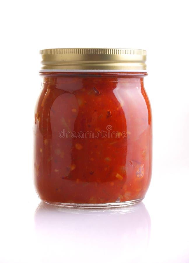 Preserved tomato relish. A sealed jar of Tomato Relish isloated on white background stock photo
