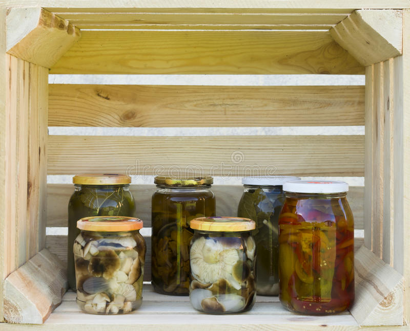 Preserving pickled cucumbers and mushrooms. Pickles jars. royalty free stock photography