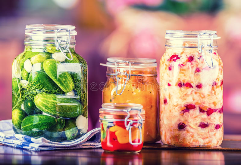Preserving. Pickles jars. Jars with pickles, pumpkin dip, white cabbage, roasted red yellow pepper. Pickled Vegetables. Vegetable being prepared for preserving royalty free stock photo