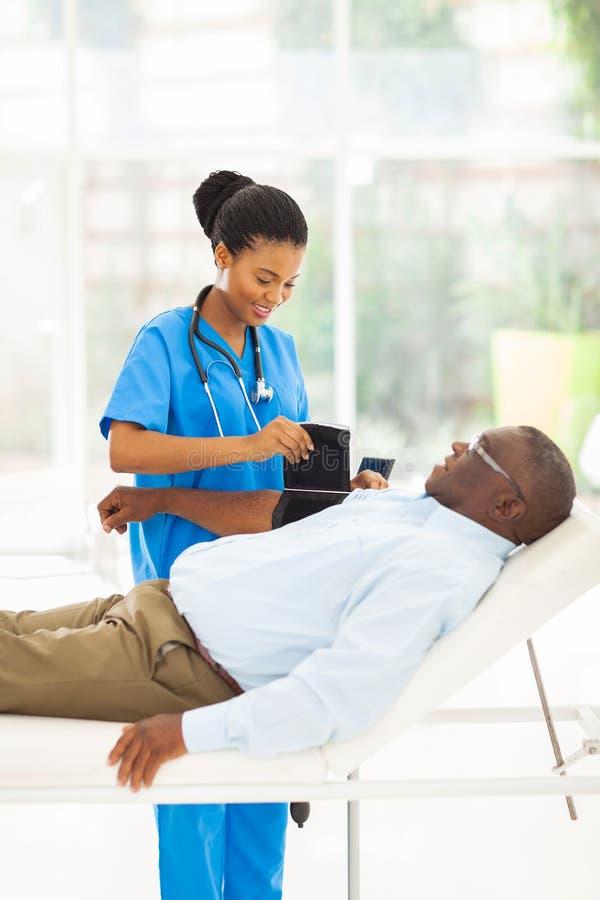 Presión arterial de medición de la enfermera africana foto de archivo