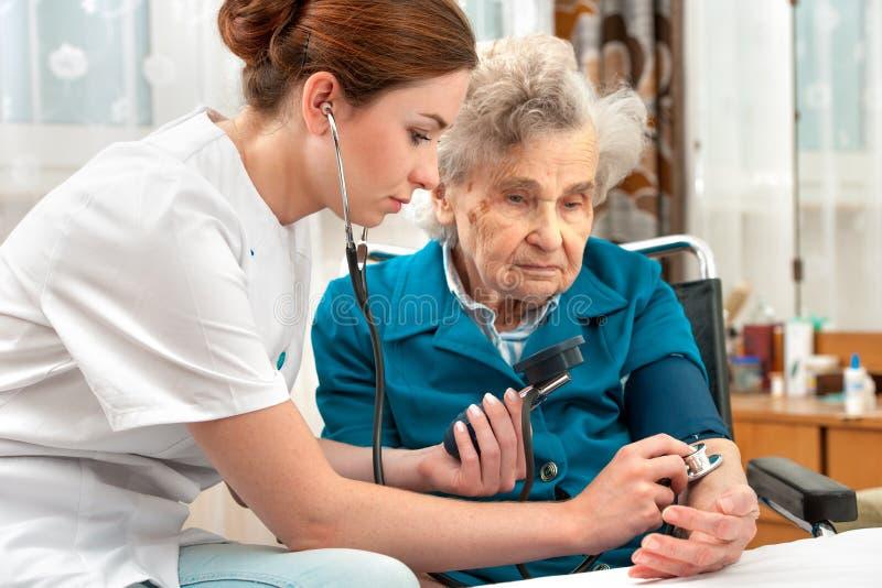 Presión arterial de medición de la mujer mayor fotos de archivo libres de regalías