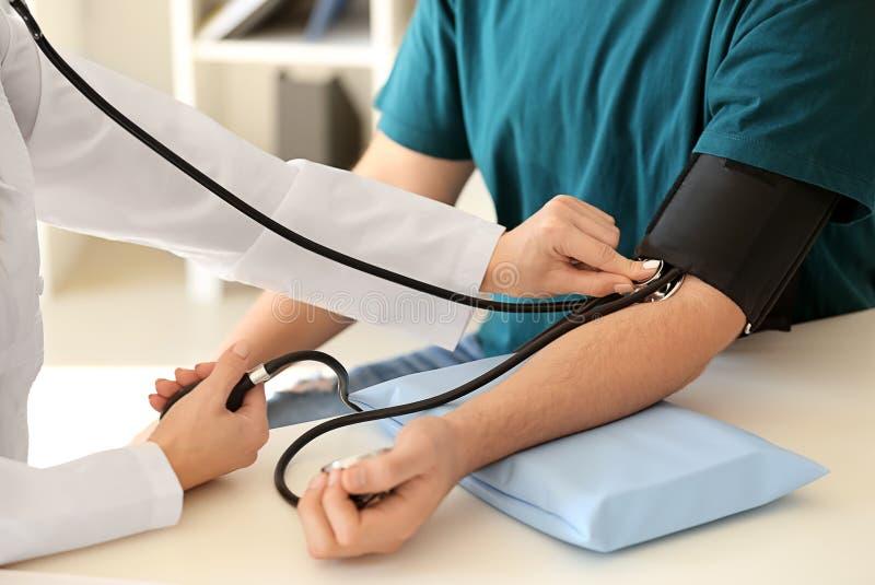 Presión arterial de medición del doctor de sexo femenino del paciente masculino en hospital imagenes de archivo