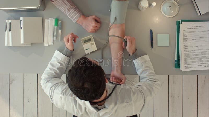 Presión arterial de medición del doctor de un paciente Visión superior imagen de archivo