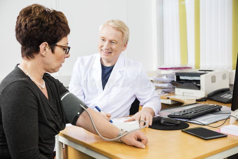 Presión arterial del doctor Checking Female Patient confiado imagen de archivo