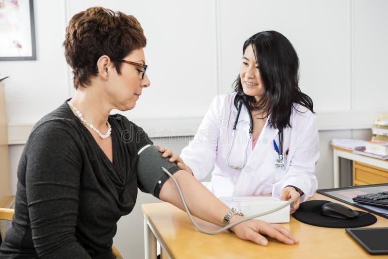Presión arterial del doctor Examining Female Patient imagen de archivo libre de regalías