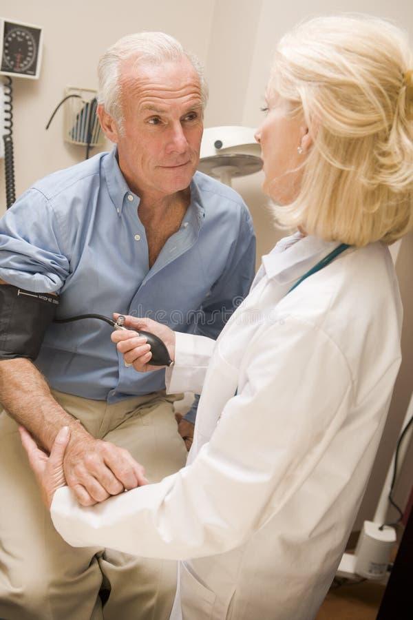 Presión arterial del doctor Measuring Mans foto de archivo libre de regalías