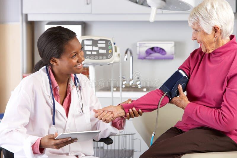 Presión arterial del doctor Taking Senior Female Patient's imágenes de archivo libres de regalías