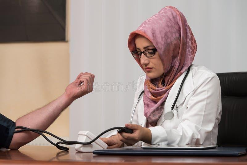 Presión arterial del doctor Taking Young Man musulmán foto de archivo